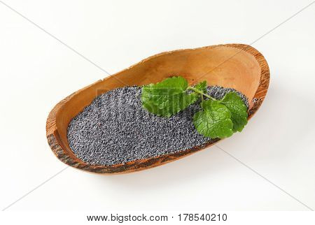 black poppy seeds in boat-shaped wooden bowl on white background