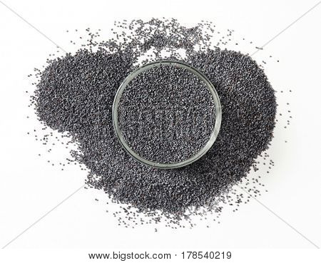 Whole black poppy seeds in glass bowl and around it