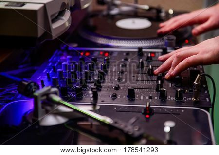 Close Up Dj Hands On Equipment Deck And Mixer With Vinyl Record At Party. Selective Focus