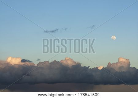 Full moon and clouds illuminated by sun at the end of the day