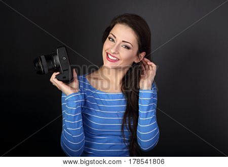 Smiling Young Female Photograph Holding Photo Camera And Looking Happy On Dark Grey Background With