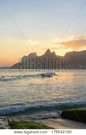Landscape of the beaches of Arpoador Ipanema and Leblon in Rio de Janeiro during dusk with the waves surfers hill Two brothers Vidigal and Gávea stone in the background