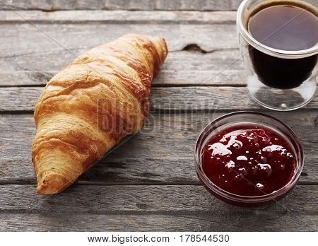croissant with jam and coffe on wooden background