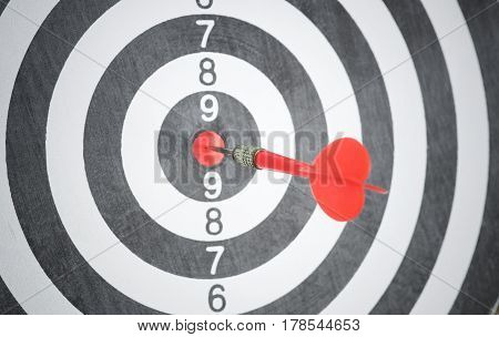 red arrow on center of dartboard. concept business goal to success.
