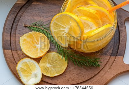 orange cool drink of lemonade with slices of orange and Mandarin in a transparent bowl of ice and fir-tree branch on wooden stand