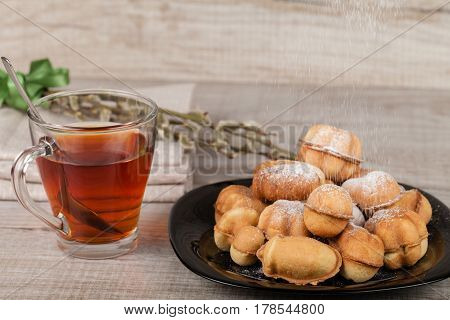 Homemade cookies with condensed milk stuffed with nuts covered with powdered sugar and a cup of tea