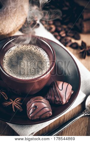 Cup fragrant hot coffee with bean chocolate sweet and loaf in vintage rustic style cinnamon steam smoke on wooden board for bracing morning breakfast.