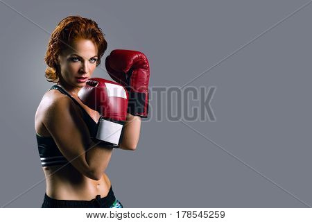 Portrait of woman in Boxing gloves on a gray background.