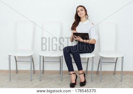 The girl sits on chair and fills up the documents
