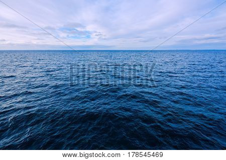 Blue seascape background wide angle view of the sea surface on cold winter day