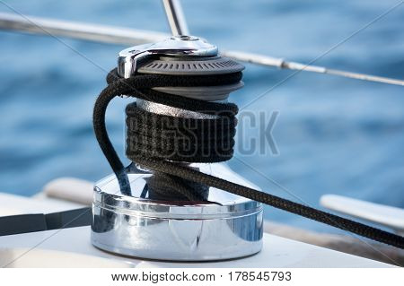 Sailboat winch and rope yacht detail. sea in background