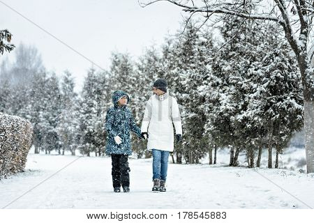 mother and daughter smiling, holding hands and going on a winter road