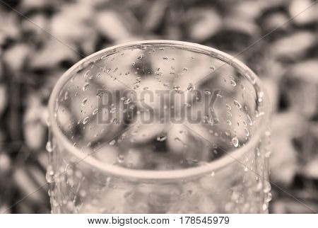 close photo of an empty glass covered with drops of water in the garden in ochre tones