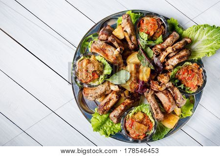 Meat plate with delicious pieces of meat salad lamb ribs grilled vegetables and sauce. Top view and wooden table