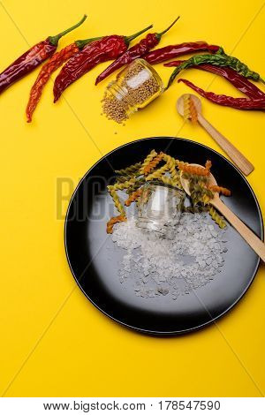 Salt Crystals Spilled On Black Plate And Dried Fusilli Pasta