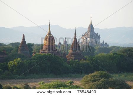 Tops of ancient Buddhist temples in an evening haze. Bagan, Myanmar