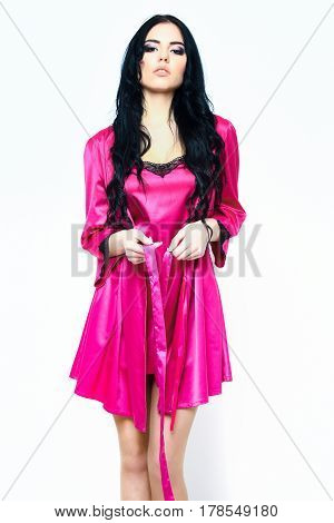 pretty cute sexy girl or beautiful woman with fashion makeup on serious face and curly long hair posing in pink or fuchsia silk robe isolated on white background