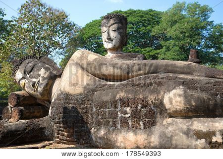 Two ancient sculptures of Buddha in ruins of Wat Phra Kaeo, sunny day. Kamphaeng Phet, Thailand