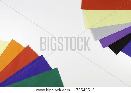 Selection of colorful felt sheets arranged as border frame on white background. Top view