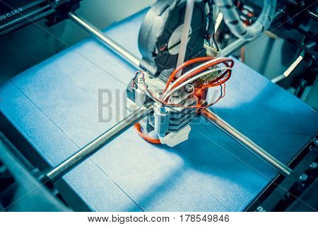 Work 3d printer close. Printing 3D printer Object Orange plastic On blue background. Plastic Wire Filament, Modern printing technology. Progressive additive technology