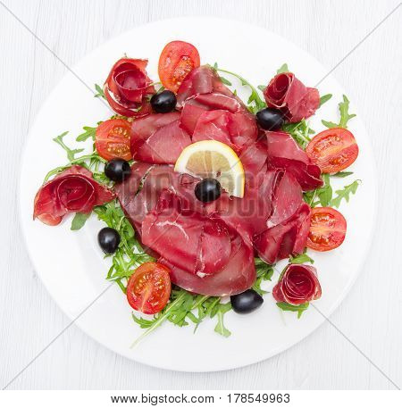 a dish of bresaola and aragula and olives