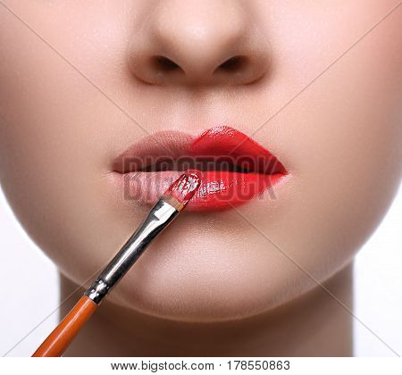 Make-up artist apply lipstick with brush. Close-up of female model face with fashion glossy red lips makeup, beauty concept