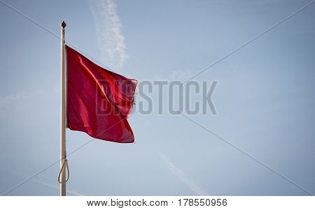 A red UK coast guard flag indicating that it is unsafe to enter the water; set against blue sky copy space.