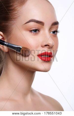 Beauty, cosmetics, finish make-up, powder brush. Woman applying base foundation primer on face, white background