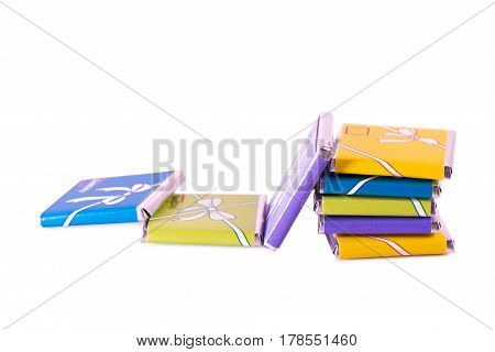 Small Chocolates In Colorful Wrappers Isolated On White Background. A Fallen Tower.