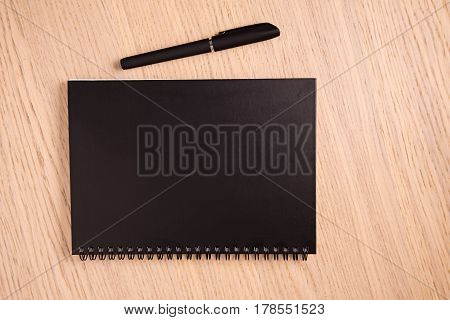 A Black Notebook In The Closed State Rests On A Wooden Background. Next To Him A Pen.