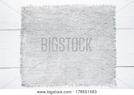 Background of wood planks painted in white and burlap