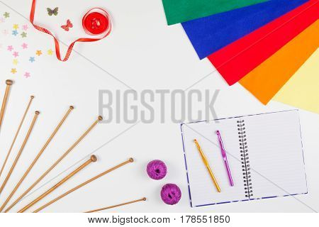 Handicraft background. Knitting, sewing and crochet tools with paper notebook on white background. Top view