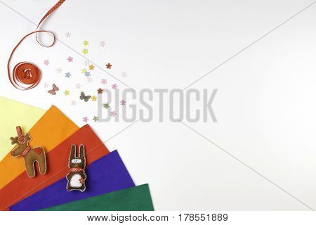 Colorful felt, sewing accessories and handmade felt toys on white background. Top view