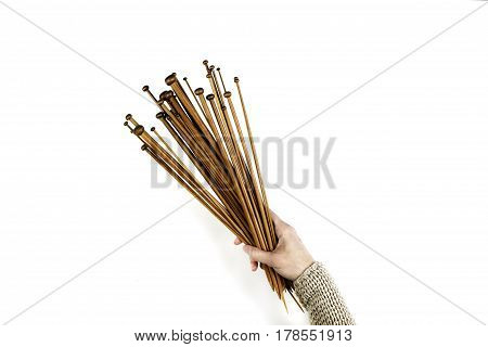 Woman hand holding a lot wooden knitting needles on white background. Top view