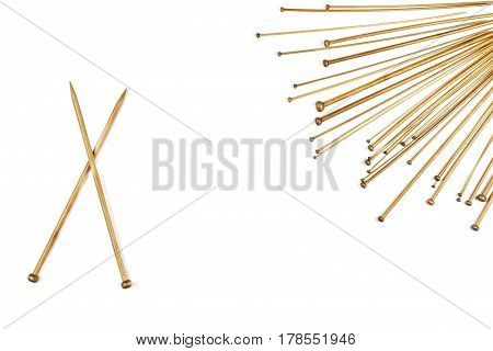 Variety of bamboo knitting needles in different sizes on white background. Top view