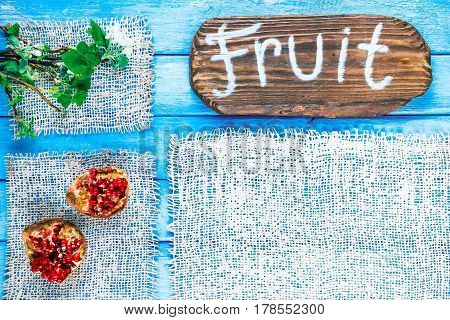 Background of narrow wood planks painted in blue. Bunch of blooming apple tree and young black current twigs. Pomegranates in the corner. Wood signboard with text 'Fruit' as title bar