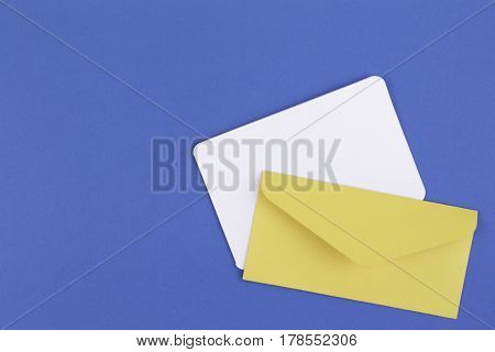 Colorful yellow envelope and white card on blue background. Top View.