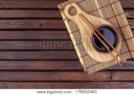 Background for sushi. Bamboo mat, soy sauce, chopsticks on wooden table. Top view with copy space