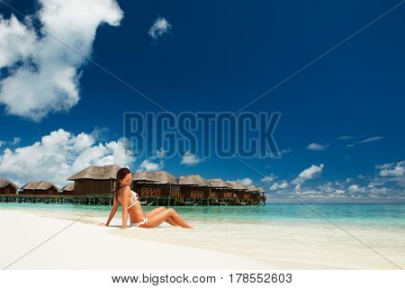 Sexy woman relax on the summer beach. Happy lifestyle. White sand, blue sky and crystal sea of tropical beach. Vacation at Paradise. Ocean beach relax, travel to islands