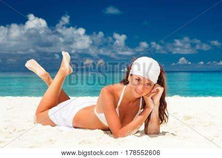 Fashion woman relaxing on the beach. Happy lifestyle. White sand, blue sky and crystal sea of tropical beach. Vacation at Paradise. Ocean beach relax, travel to islands