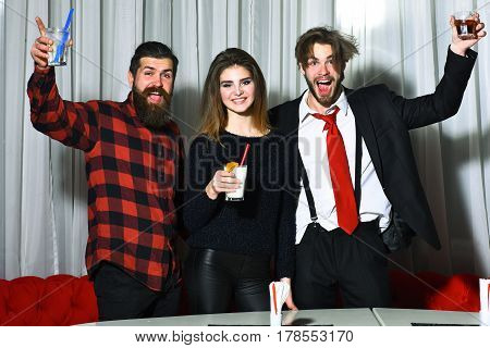 Happy friends pretty girl and two bearded men hipsters with beard in red plaid shirt and business suit smiling and celebrating with cocktails and alcohol drinks at party in cafe on white curtain