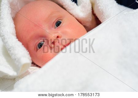 Adorable baby boy looking out under white towel.