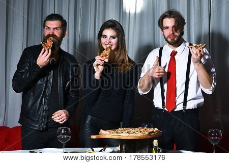 Happy friends pretty girl and two bearded men hipsters with beards smiling and eating tasty pizza slices at party in pizzeria cafe or restaurant on white curtain