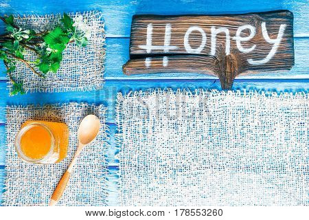 Background of narrow wood planks painted in blue. Bunch of blooming apple tree and young black current twigs. Honey jar in the corner. Wood signboard with text 'Honey' as title bar