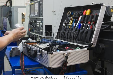 Worker in industry holding set of tools for repair - screwdriver, voltmeter, wrenches, close up
