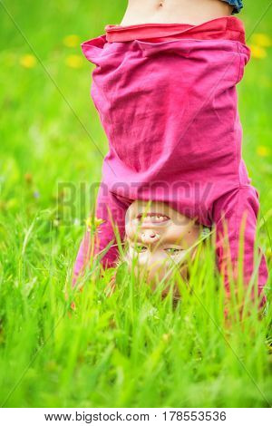 Happy little girl standing upside down on green grass in summer park