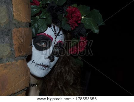 Attractive young woman dressed in a Mexican day of the dead inspired costume, peering from behind a brick wall.