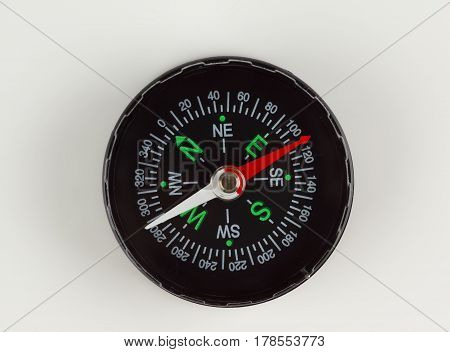 round magnetic compass with bright symbols lies on the table