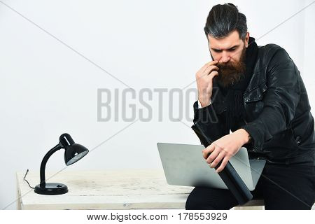 Bearded man long beard. Brutal caucasian unshaven hipster sitting on table with lamp and bottle on holding laptop in black leather jacket isolated on white studio background copy space