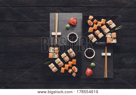 Japanese food restaurant, salmon sushi and roll platter. Set for two with chopsticks, ginger, soy, wasabi. Top view on rustic wood background and black slate plates. Vintage filter
